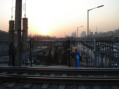 Beijing skyline seen from a railway bridge illegally used by pedestrians to cross the highway.